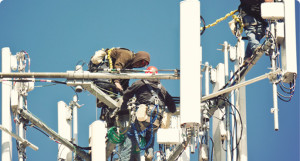 Two men on top of a telecommunications tower.