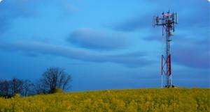 A wireless telecommunications tower in a grass field.